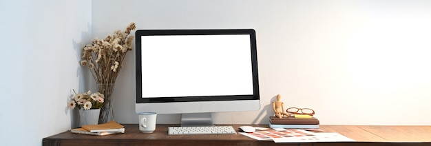 Um espaço de trabalho de madeira é cercado por um monitor de computador com tela branca em branco e vários equipamentos.