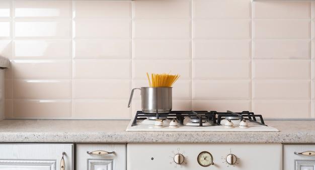 Um espaguete sendo cozido na panela em água fervente no fogão na cozinha