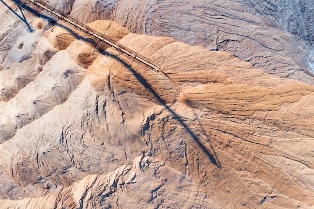 Um espalhador industrial em processo de trabalho. o processo de derramar pilhas de rochas