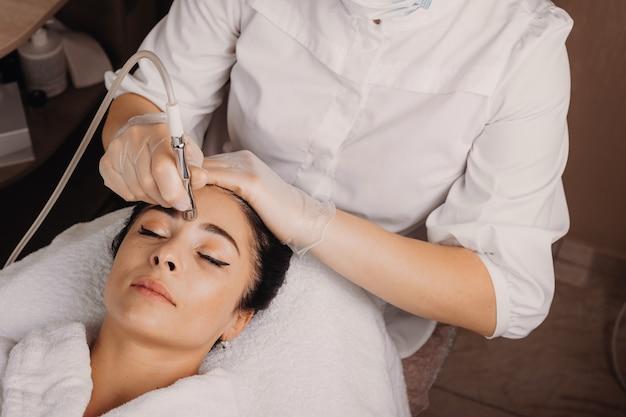 Um especialista em spa está fazendo uma massagem facial com uma senhora caucasiana deitada no sofá