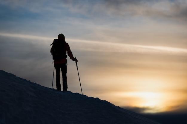 Um esquiador alpinista vê o sol se pôr
