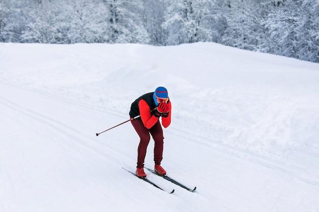 Um esquiador com um agasalho esportivo vermelho, balaclava azul e óculos de segurança descendo rapidamente