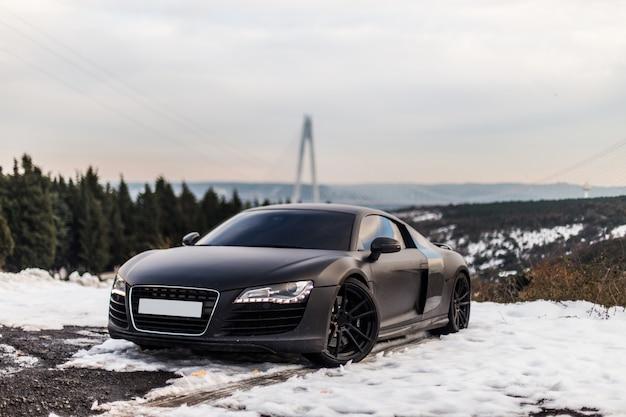 Um estacionamento preto luxuoso do cupê do esporte na estrada nevado na floresta.