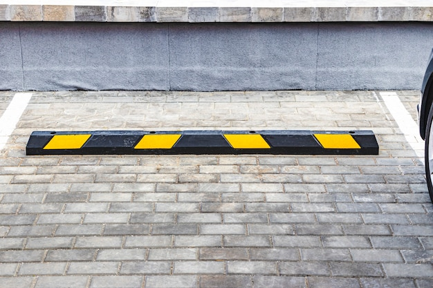 Um estacionamento vazio em uma área residencial com paradas amarelas para carros. fechar-se. pare o limitador de estacionamento.