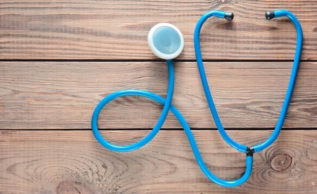 Um estetoscópio azul em uma mesa de madeira. equipamento de cardiologia médica. vista do topo.