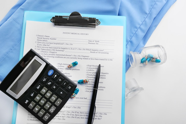 Um estetoscópio, casaco, calculadora e prancheta, close-up