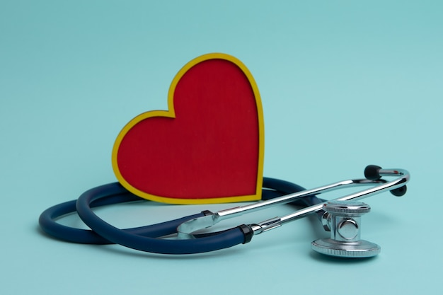Um estetoscópio e um coração vermelho sobre um fundo azul. o conceito de cardiologia.
