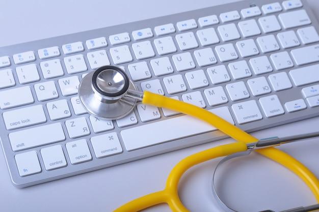 Um estetoscópio médico perto de um laptop em uma mesa de madeira