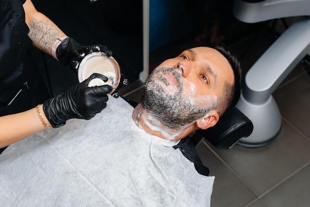 Um estilista profissional em uma barbearia moderna e estilosa faz a barba e corta o cabelo de um jovem. salão de beleza, cabeleireiro.