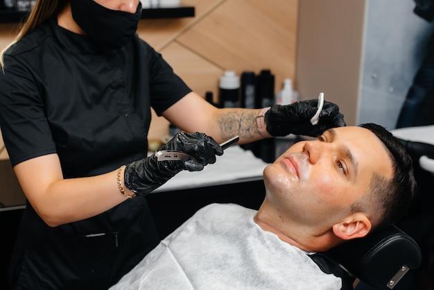 Um estilista profissional em uma barbearia moderna e estilosa faz a barba e corta o cabelo de um jovem. salão de beleza, salão de cabeleireiro.