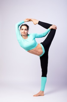 Um estiramento do treinador da jovem mulher em um fundo isolado branco no estúdio. o conceito de esportes e meditação. treinamento para alongamento
