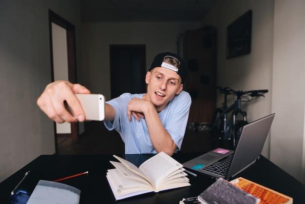 Um estudante adolescente sorridente fazendo selfie enquanto estudava em casa atrás de uma mesa na sala. taxas de selfies.