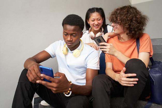 Um estudante afro-americano conversa sozinho e seus colegas riem enquanto usam seus telefones celulares