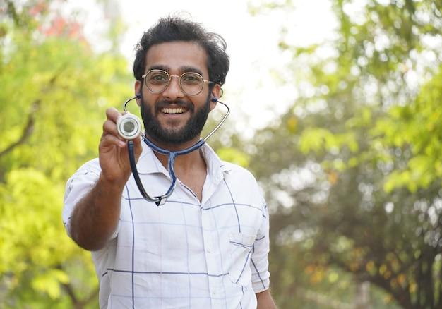 Um estudante animado mostrando o estetoscópio - estudante universitário com estetoscópio e mostrando o sinal de sucesso - conceito de educação médica