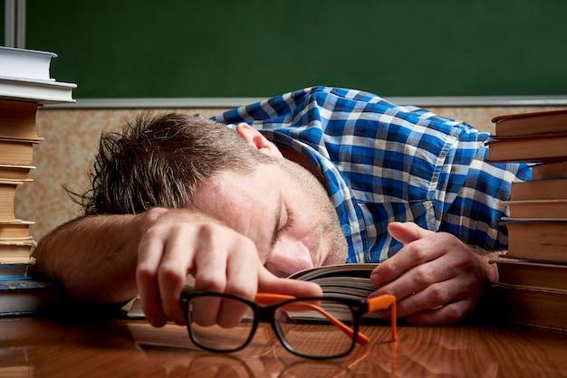 Um estudante cansado está dormindo em uma mesa com pilhas de livros.