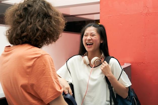 Um estudante chinês fala e ri com um colega de escola