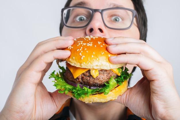 Um estudante com muita fome come fast food.