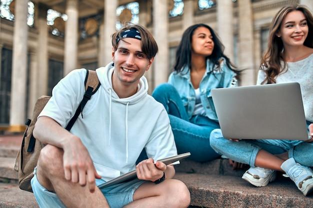 Um estudante com um laptop e uma mochila senta-se na escada perto do campus e se comunica com os amigos.