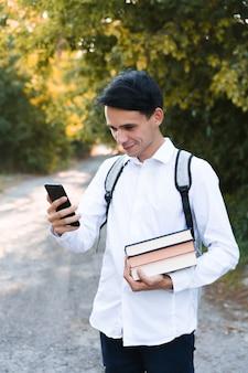 Um estudante de cabelos escuros, vestido com uma camisa branca e limpa, com uma pasta cinza sobre os ombros, segura um telefone e livros multicoloridos sobre um fundo de outono.