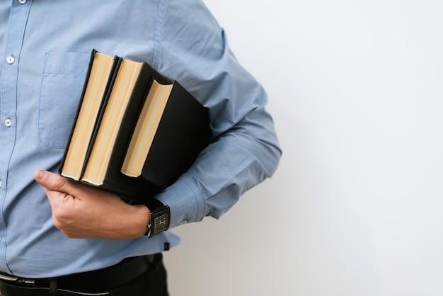 Um estudante de camisa azul e calça social segura uma pilha de livros. o conceito de treinamento, busca de idéias, soluções de negócios