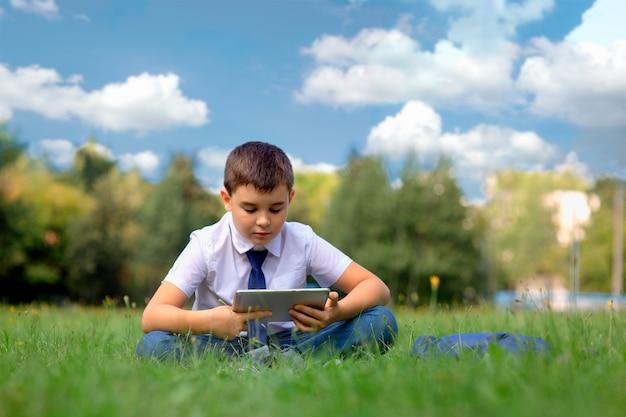 Um estudante de camisa branca e gravata azul está sentado na grama verde contra um céu azul com nuvens brancas e joga um tablet