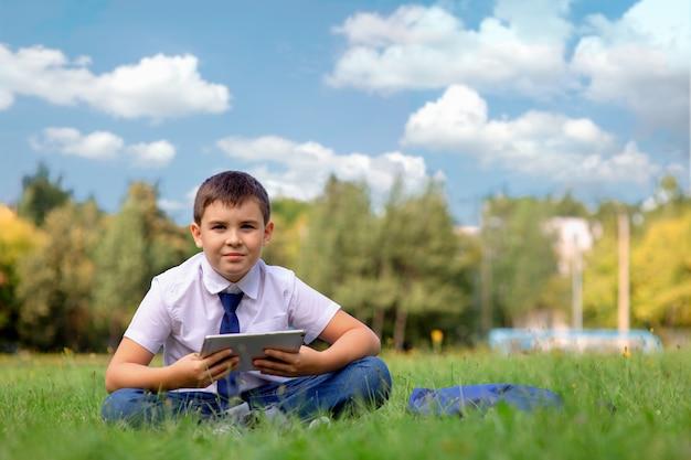 Um estudante de camisa branca e gravata azul está sentado na grama verde contra um céu azul com nuvens brancas e segura um tablet.