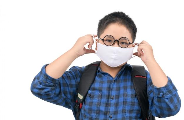 Um estudante de ensino médio usando máscara e óculos, carregando mochila isolada
