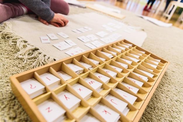 Um estudante de uma escola montessori usando cartões com letras