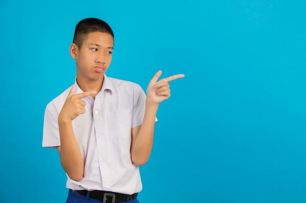 Um estudante do sexo masculino asiático com uma mão levantou o gesto apontando contra o azul.