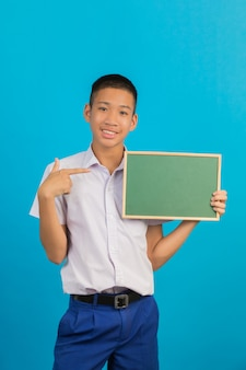 Um estudante do sexo masculino asiático masculino com um gesto das mãos levantadas e apontadas com uma placa verde segurando a outra mão no azul.