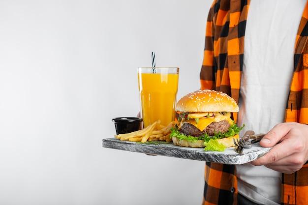 Um estudante do sexo masculino está segurando placa com um hambúrguer fresco.
