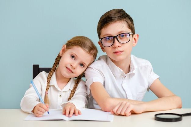 Um estudante e uma menina estudam em casa e fazem a lição de casa.