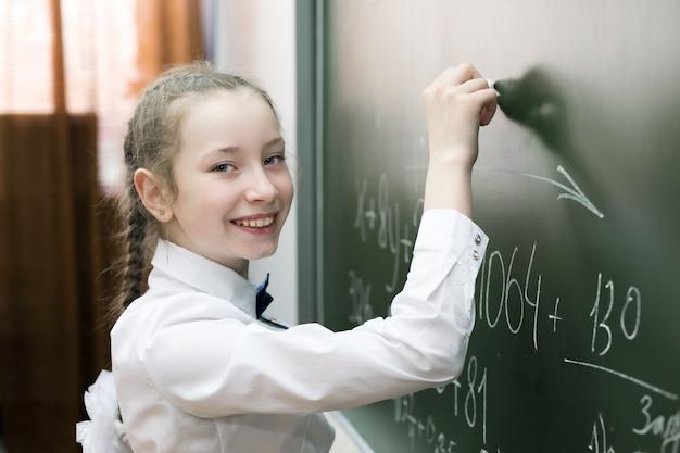 Um estudante fêmea da menina da escola primária escreve no quadro-negro.