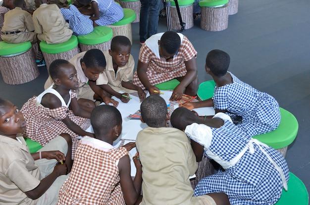 Um estudante ivoirien de 8 anos de idade desenhando em papel branco.