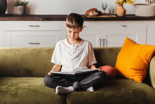 Um estudante lê um livro no sofá da sala de estar