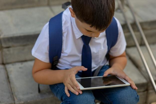 Um estudante moreno com uma mochila nas costas se senta na escada e joga um tablet. fechar-se