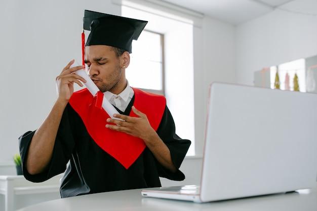 Um estudante negro com vestido de pós-graduação e boné quadrado que está feliz por terminar seus estudos beija a tão esperada cerimônia de formatura online do diplomaon