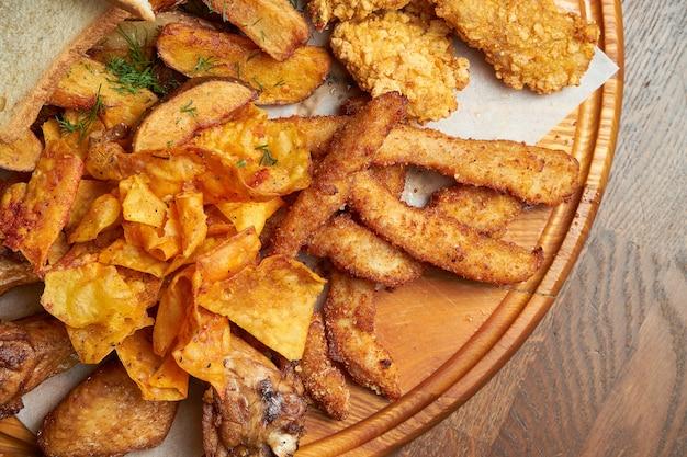 Um excelente lanche de cerveja é um conjunto de batatas nuggets de frango com molho de pergaminho em uma bandeja de pedra. comida de bar. fechar-se.
