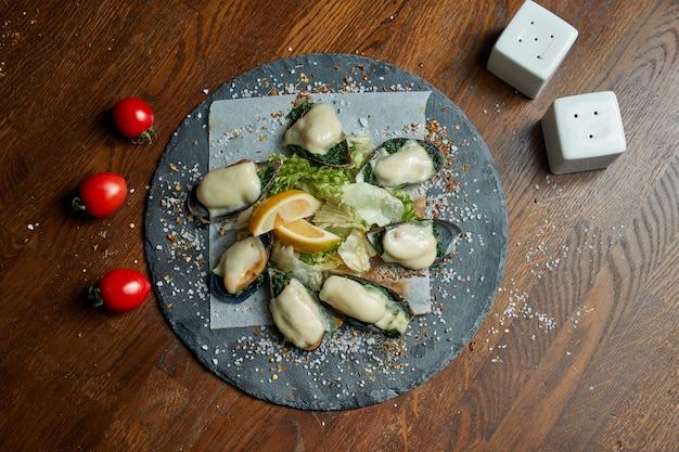 Um excelente lanche de cerveja é um conjunto de mexilhões assados com molho de natas, queijo e cebola em uma bandeja de pedra. comida de bar. frutos do mar. mexilhões da nova zelândia