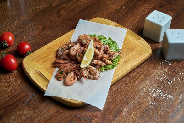 Um excelente lanche de cerveja é um conjunto de pequenas batatas fritas de camarão em pergaminho em uma bandeja de madeira. comida de bar. fechar frutos do mar