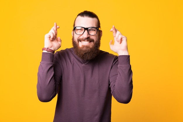 Um excitado jovem barbudo de óculos espera que seus sonhos se tornem realidade perto de uma parede branca