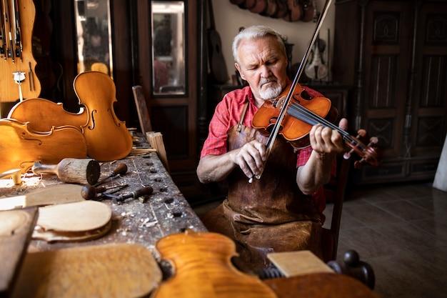 Um experiente marceneiro de cabelos grisalhos, usando avental de couro e sentado em sua oficina de marcenaria tocando violino