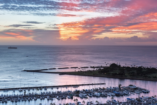 Um extenso pôr-do-sol sobre iates do porto de barcos pequenos ala wai e da ilha da magia em haw