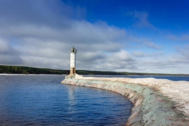 Um farol com tempo ensolarado farol no quebra-mar farol no lago