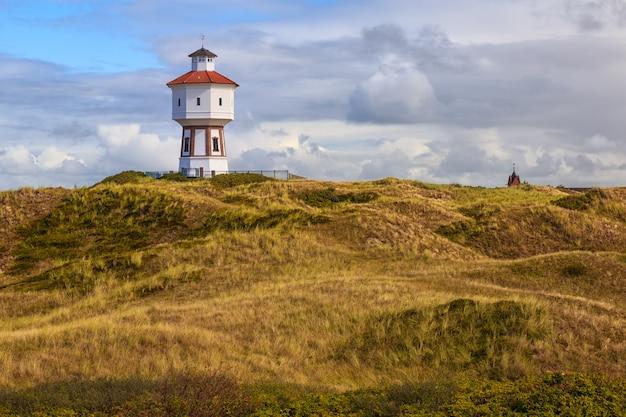 Um farol e uma torre de água na ilha de langeoog, baixa saxônia, alemanha