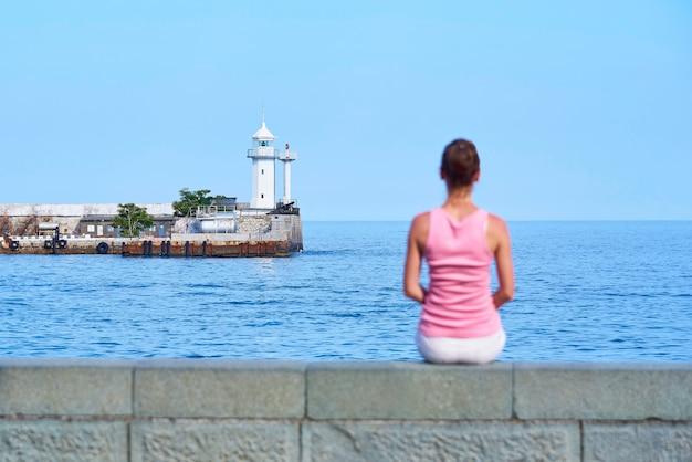 Um farol no mar e uma garota embaçada na praia.