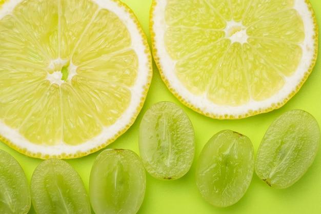 Um fatias de limão e bagas de uvas brancas sobre um fundo de cor verde claro.