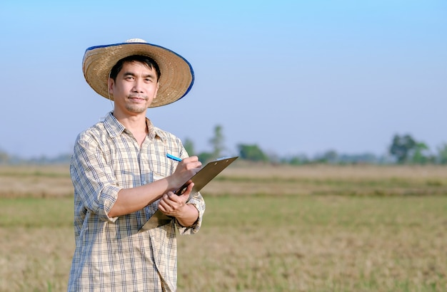 Um fazendeiro asiático em um campo de arroz com um quadro de papel escrevendo uma mensagem sobre o produto