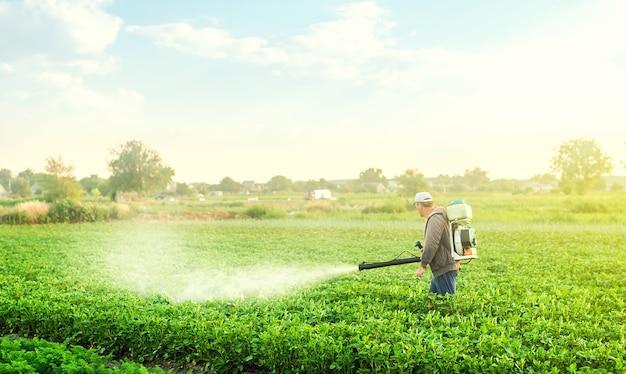 Um fazendeiro com um pulverizador de névoa caminha pela plantação de batata