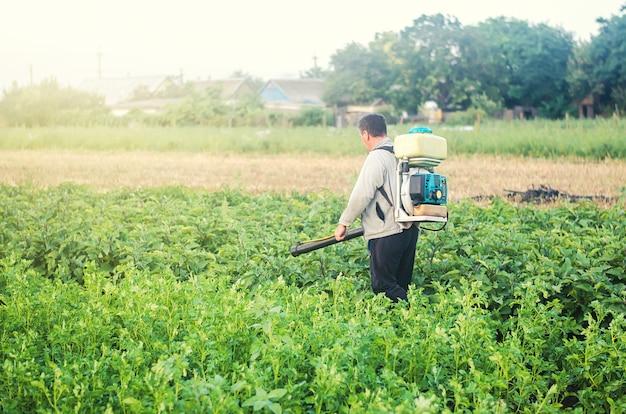 Um fazendeiro com um pulverizador de névoa processa a plantação de batata contra pragas e infecções por fungos